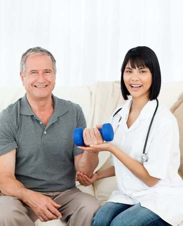 Nurse helping her patient to do exercises at home Stock Photo - 10217589