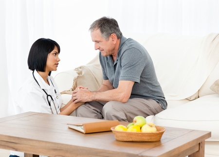 carer: Man talking with his nurse on the sofa