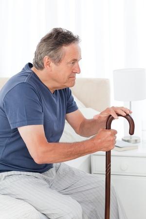 Hombre maduro reflexivo con su bastón en su cama en su casa