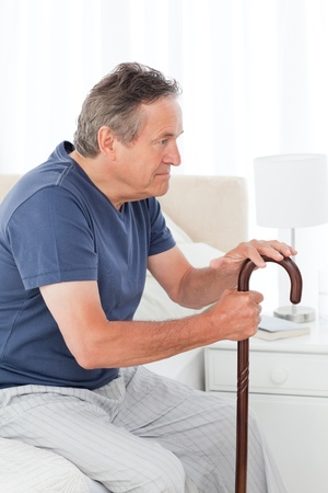 guy with walking stick: Mature man thoughtful with his walking stick on his bed at home