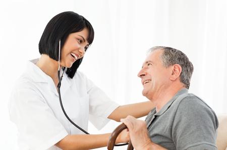 enfermera con paciente: Hombre maduro con su enfermera mirando el port�til en casa Foto de archivo