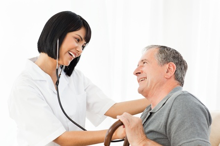 Mature man with his nurse looking at the laptop at home Stock Photo - 10212786