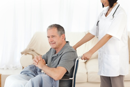 Man in his wheelchair with his nurse at home Stock Photo - 10218815