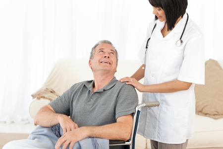 Man in his wheelchair with his nurse at home Stock Photo - 10218803