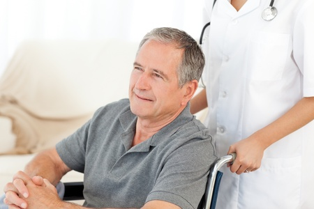 Man in his wheelchair with his nurse at home photo