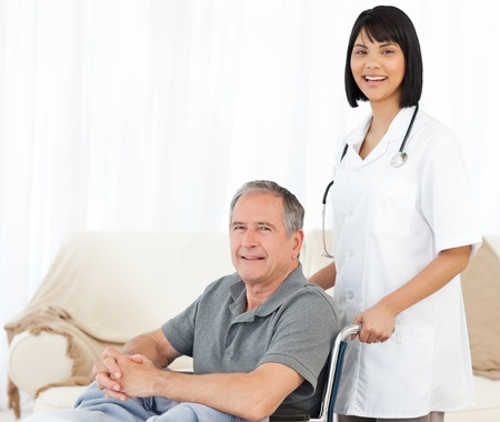 Man in his wheelchair with his nurse at home Stock Photo - 10214614