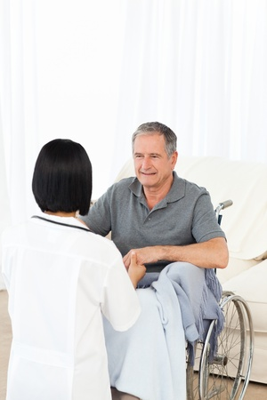 Man in his wheelchair with his nurse at home Stock Photo - 10218359
