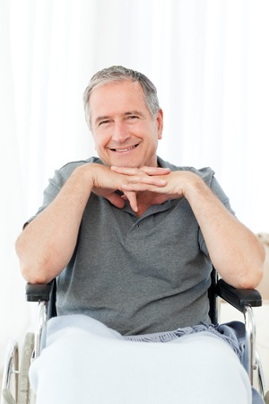 Retired man in his wheelchair at home photo
