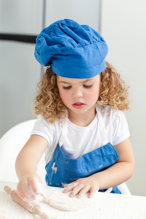 Little girl baking in the kitchen at home photo
