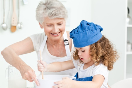 A little girl  baking with her grandmother at home photo