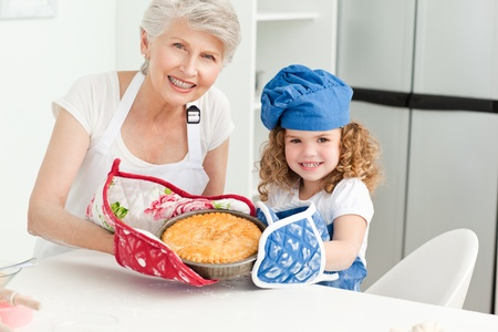 A little girl with her grandmother looking at the camera at home photo