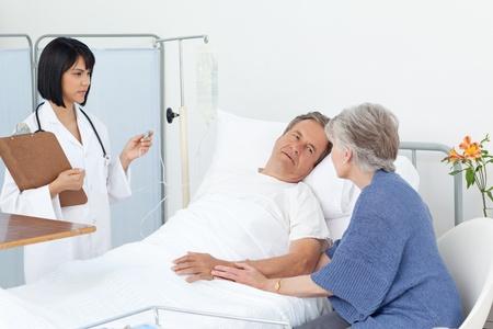 malade au lit: Un homme m�r avec son �pouse dans un h�pital