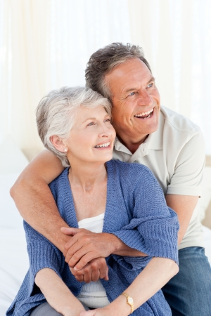 Senior couple hugging on their bed at home photo