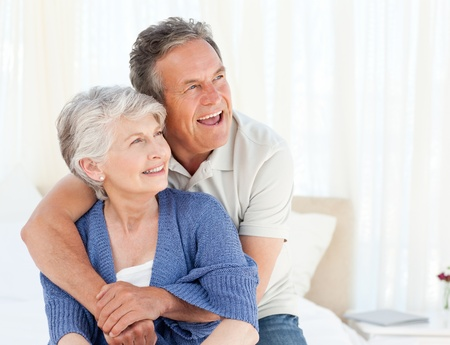 Senior couple hugging on their bed at home Stock Photo - 10220035