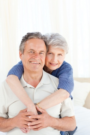 an elderly couple: Senior couple hugging on their bed at home