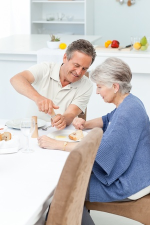 male senior adult: Retired couple eating  in the kitchen