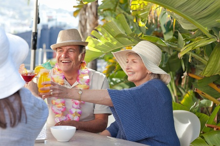 vacation destinations: Retired woman drinking a cocktail under the sun