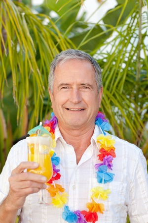Mature man drinking a cocktail under the sun photo