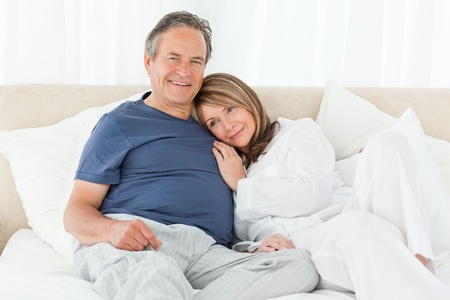 Senior couple lying down on their bed at home photo