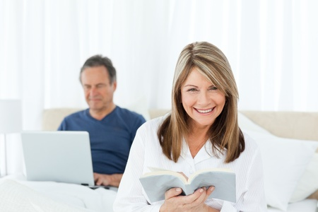 Senior looking at his laptop while her wife is reading at home photo