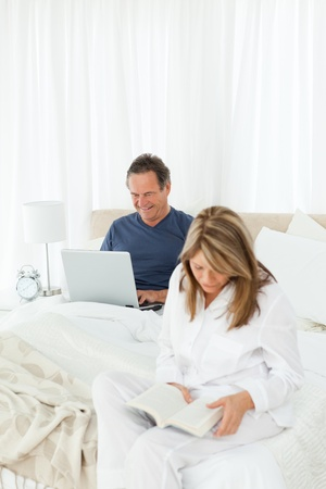 Happy woman reading a book while her husband is using a laptop in the room photo