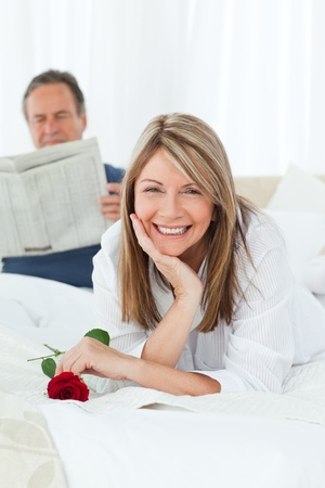 Happy woman with her rose while her husband is reading a newspaper at home photo