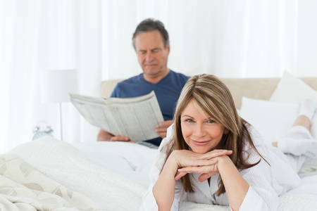 Smiling woman looking at the camera while her husband is reading at home photo