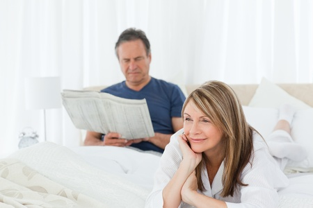 Woman smiling while her husband is reading at home photo