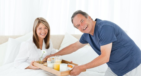 Lovely couple  having breakfast in their bed at home photo