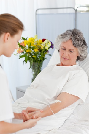 Nurse putting a drip on the arm of her patient Stock Photo - 10170456