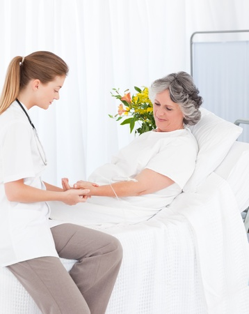Nurse putting a drip on the arm of her patient Stock Photo - 10206307