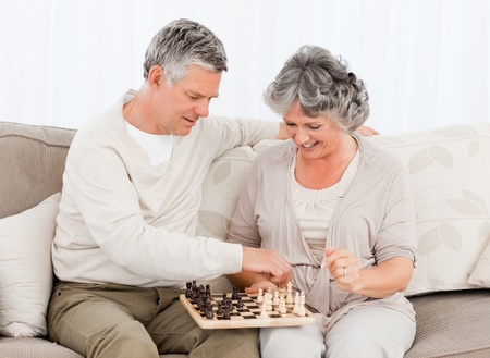Couple playing chess on their sofa at home photo
