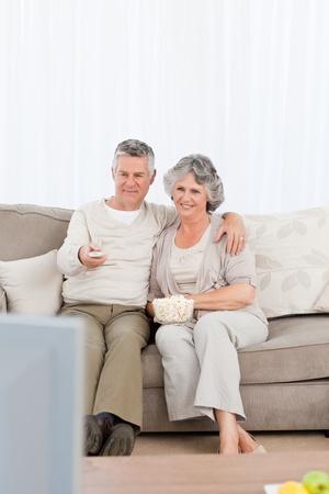 Junges Paar vor dem Fernseher in ihrem Wohnzimmer zu Hause