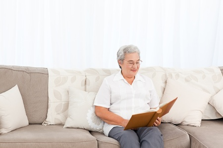 Woman looking at her photo album at home Stock Photo - 10218662