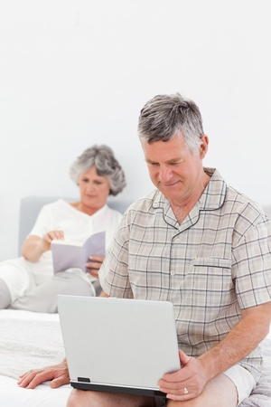 Man working on his laptop while his wife is reading at home photo