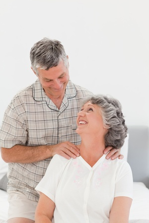 an old couple: Retired man giving a massage to his wife at home Stock Photo