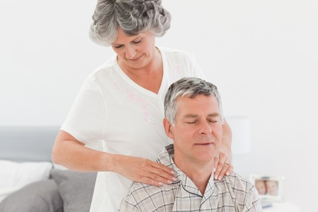 Retired woman giving a massage to her husband at home Stock Photo - 10215168