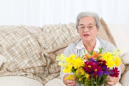Senior with flowers  at home Stock Photo - 10214026