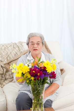 Senior with flowers  at home Stock Photo - 10215308