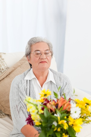 Senior with flowers  at home Stock Photo - 10215475