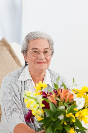 Mature woman sitting on the sofa with the flowers at home Stock Photo - 10219561