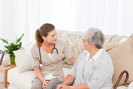 Nurse taking the heartbeat of her patient at home Stock Photo - 10220030