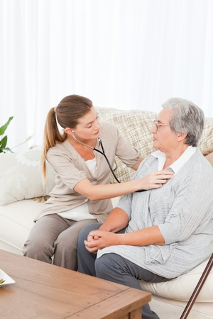 Nurse taking the heartbeat of her patient at home photo