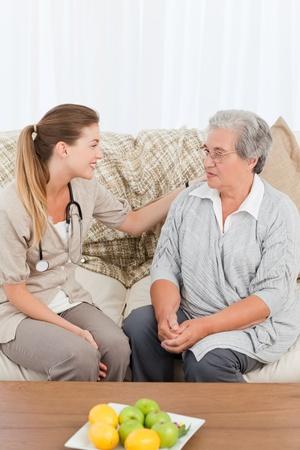 empleadas domesticas: Enfermera de tomar el pulso de su paciente en el hogar Foto de archivo
