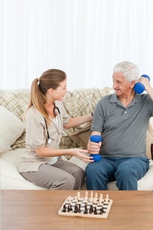 Lovely nurse helping her patient to do exercises at home Stock Photo - 10220187
