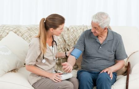 enfermera con paciente: Una enfermera encantadora ayudar a su paciente a hacer ejercicios en casa