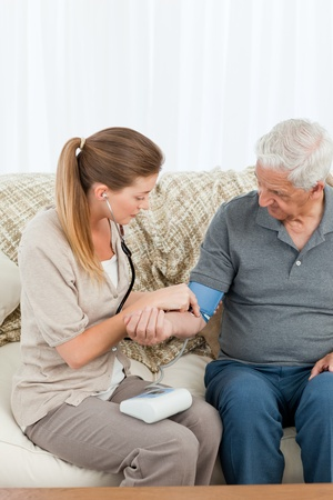 Lovely nurse helping her patient to do exercises at home photo