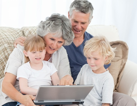 Adorable family looking at the laptop at home photo