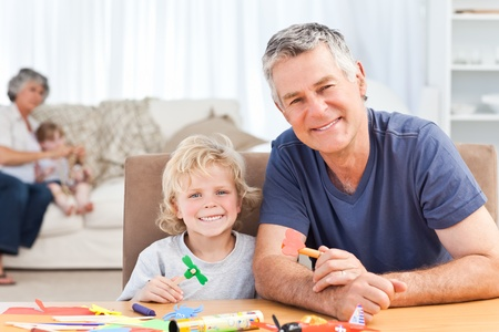 Little boy drawing with his grandfather at home photo