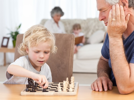 Young boy playing chess with his grandfather at home photo